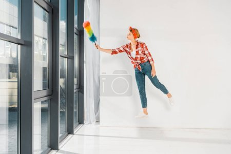 floating girl in jeans and plaid shirt cleaning windows with duster