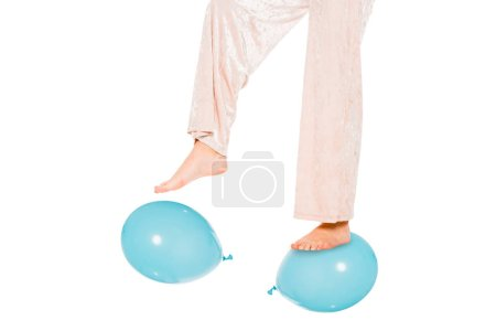 Photo pour Vue partielle de la jeune fille en lévitation dans l'air, debout sur des ballons bleus - image libre de droit