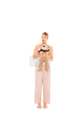 Photo for Floating girl in pyjamas holding teddy bear isolated on white - Royalty Free Image