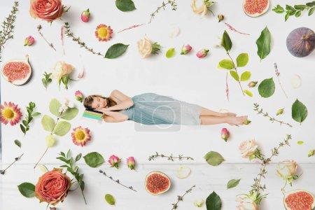 Foto de Chica en vestido azul durmiendo en libro en aire entre Ilustración flores - Imagen libre de derechos