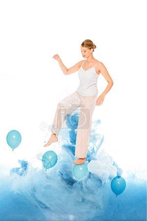 Photo pour Fille en pyjama debout sur des ballons bleus avec illustration de nuage - image libre de droit