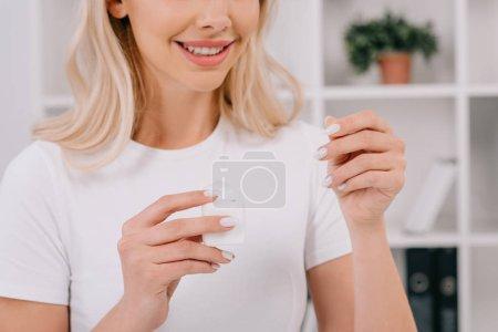 Photo pour Recadrée vue de femme souriante tenant la soie dentaire - image libre de droit