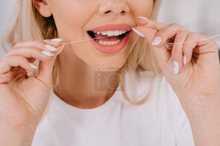 Photo pour Vue recadrée de la soie dentaire femme dents avec fil dentaire - image libre de droit