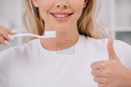 Photo pour Vue recadrée de femme en chemise blanche en tenant la brosse à dents et affichage de pouce pancarte - image libre de droit