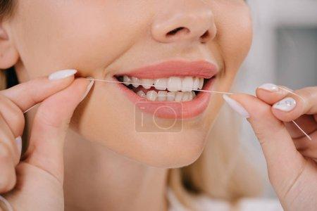 Photo pour Vue partielle des dents de soie dentaire femme avec fil dentaire - image libre de droit