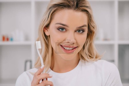 Photo for Beautiful smiling woman holding toothbrush and looking at camera - Royalty Free Image