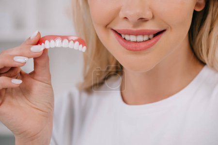 Photo for Cropped view of smiling woman holding teeth cover - Royalty Free Image