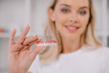 Selective focus of teeth cover with smiling woman ...