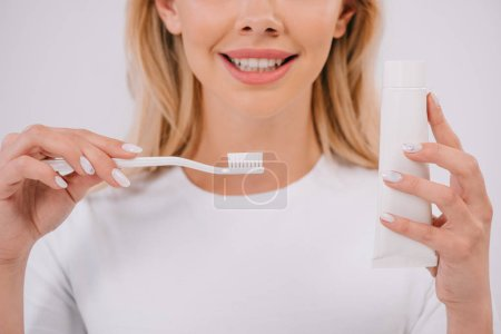 Foto de Vista recortada de la mujer sonriente sosteniendo cepillo de dientes y pasta de dientes con espacio de copia aislado en blanco - Imagen libre de derechos