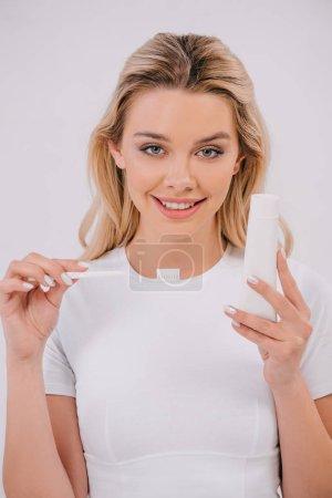 Foto de Hermosa mujer mirando a la cámara mientras sostiene el cepillo de dientes y pasta de dientes con espacio de copia aislado en blanco - Imagen libre de derechos