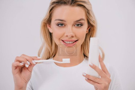 Photo for Beautiful woman looking at camera while holding toothbrush and toothpaste with copy space isolated on white - Royalty Free Image