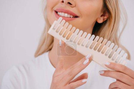 Photo pour Vue partielle de la femme souriante tenant la palette de couleurs des dents isolées sur blanc, concept de blanchiment des dents - image libre de droit