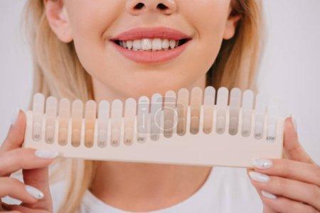 Photo pour Vue recadrée d'une femme souriante tenant une palette de couleurs isolée sur blanc, concept de blanchiment des dents - image libre de droit