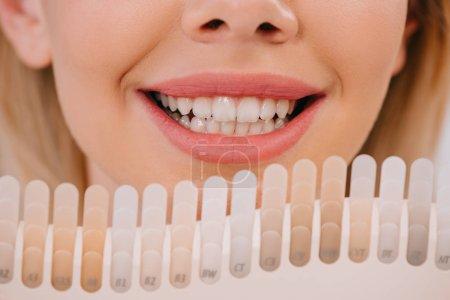 Photo pour Vue recadrée de la femme souriante tenant la palette de couleurs des dents, concept de blanchiment des dents - image libre de droit