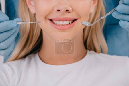 Photo pour Vue recadrée du dentiste tenant miroir buccal et sonde dentaire près d'une femme souriante - image libre de droit