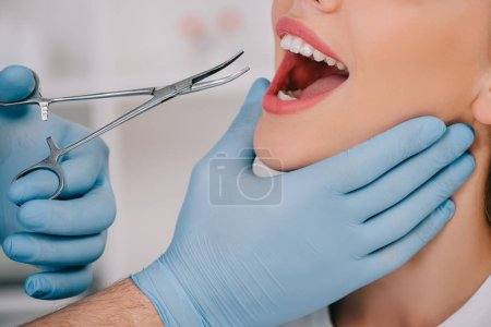Photo for Cropped view of dentist in latex gloves with dental instrument examining teeth of woman in clinic - Royalty Free Image