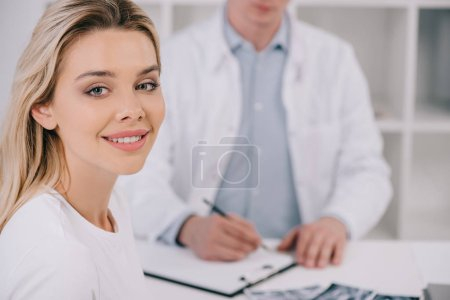 selective focus of beautiful woman looking at camera during consultation with male dentist in clinic