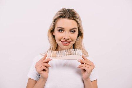 Photo pour Belle femme tenant palette de couleurs des dents isolé sur blanc, concept de blanchiment des dents - image libre de droit