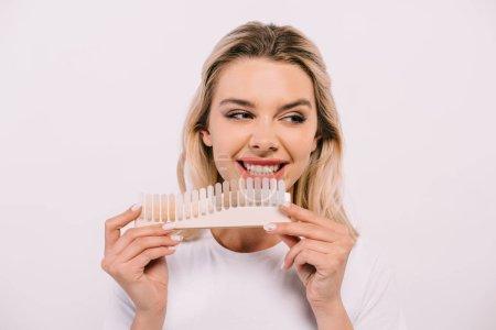 Photo pour Belle femme souriante tenant la palette de couleurs de dents isolée sur blanc, dents blanchissant le concept - image libre de droit