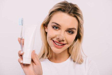 Foto de Hermosa mujer sonriente sosteniendo cepillo de dientes y pasta de dientes con espacio de copia aislado en blanco - Imagen libre de derechos