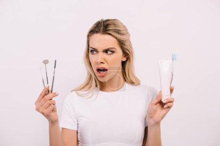 Foto de Hermosa mujer sorprendida sosteniendo pasta de dientes, cepillo de dientes e instrumentos dentales aislados en blanco - Imagen libre de derechos