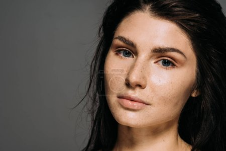 Photo for Beautiful girl with freckles on face isolated on grey - Royalty Free Image