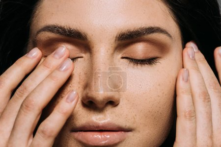 Photo for Close up view of tender girl with freckles on face touching closed eyes - Royalty Free Image