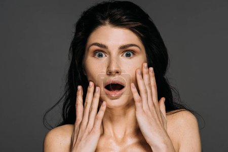 Photo for Beautiful shocked woman with freckles on face isolated on grey - Royalty Free Image