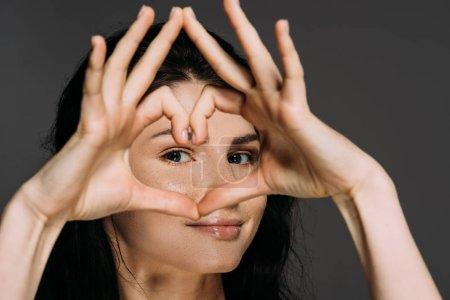 Foto de Hermosa mujer tierna mostrando signo de corazón aislado en gris - Imagen libre de derechos
