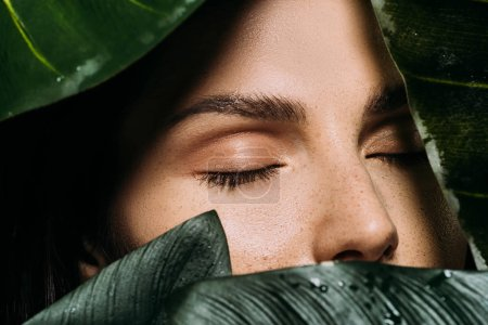 Photo for Beautiful woman with closed eyes posing with green palm leaves - Royalty Free Image