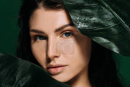 Photo pour Jolie femme avec des taches de rousseur sur le visage posant avec des feuilles de palmier isolé sur le vert - image libre de droit
