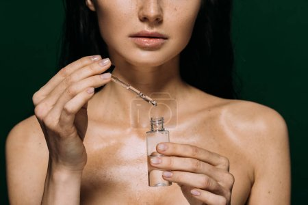 Photo for Cropped view of naked woman holding bottle with serum isolated on green - Royalty Free Image