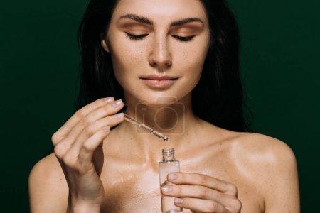 Photo pour Jolie femme nue tenant bouteille avec hydratation sérum isolé sur vert - image libre de droit