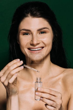 Photo for Cheerful naked girl holding bottle with moisturizing serum isolated on green - Royalty Free Image