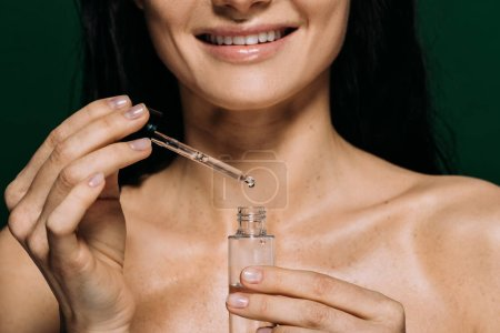 Photo for Cropped view of smiling naked woman holding pipette and bottle with serum isolated on green - Royalty Free Image