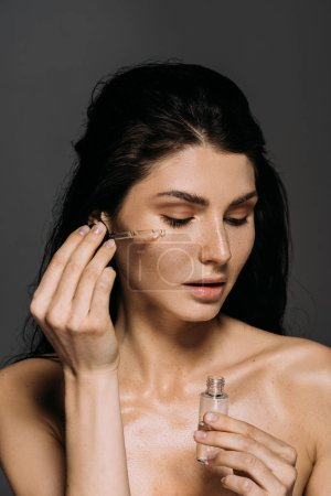 Photo for Naked brunette girl applying serum on face with pipette isolated on grey - Royalty Free Image