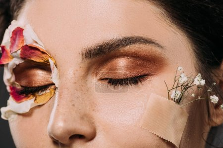 Photo pour Gros plan de femme avec fleurs sur le visage et le maquillage sur les yeux fermés - image libre de droit