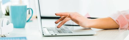 Photo for Cropped view of woman typing on laptop keyboard at workplace - Royalty Free Image