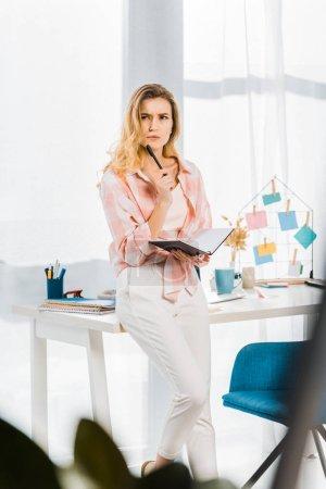 Mujer pensativa de pie en el lugar de trabajo y la celebración de cuaderno con pluma