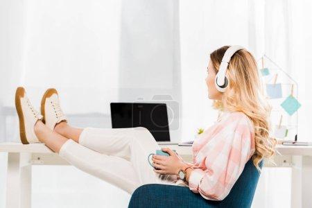 Photo pour Jeune femme détendue avec tasse de café écoutant de la musique au bureau à la maison - image libre de droit