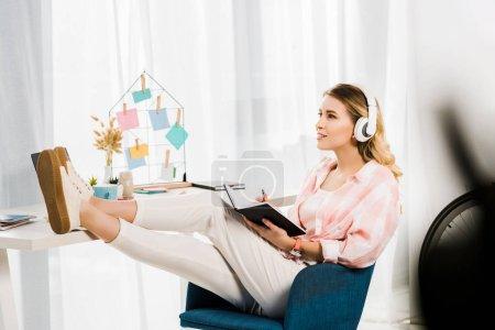 Photo pour Femme inspirée dans casque écoute la musique et l'écriture de bloc-notes avec jambes sur table - image libre de droit