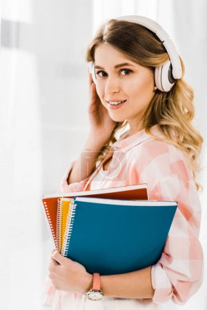 Photo for Charming girl with notebooks listening music and looking at camera with smile - Royalty Free Image