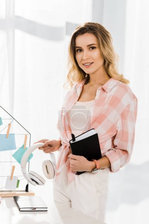 Interested woman in checkered shirt holding headphones and notebook