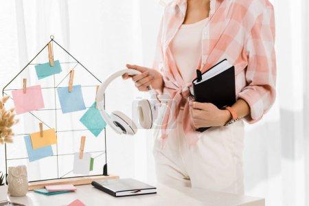 Photo pour Vue partielle de la femme en chemise à carreaux tenant écouteurs et cahier sur le lieu de travail - image libre de droit