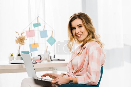 Glad young woman in checkered shirt using laptop at home office