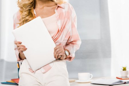Photo for Partial view of blonde woman in checkered shirt holding laptop - Royalty Free Image