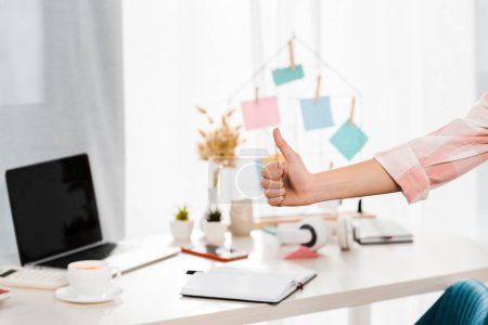 Photo pour Vue partielle de la femme, montrant le pouce vers le haut au lieu de travail - image libre de droit