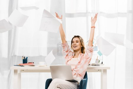 Photo pour Femme qui riante avec ordinateur portable en jetant les documents au lieu de travail - image libre de droit