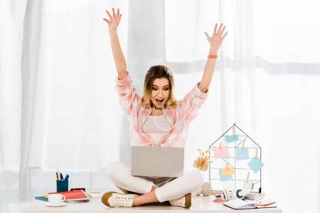 Photo pour Fille incroyable avec ordinateur portable assis sur la table et agitant les mains - image libre de droit