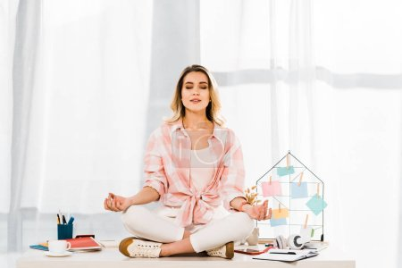 Relaxed woman in checkered shirt sitting in lotus pose at workplace